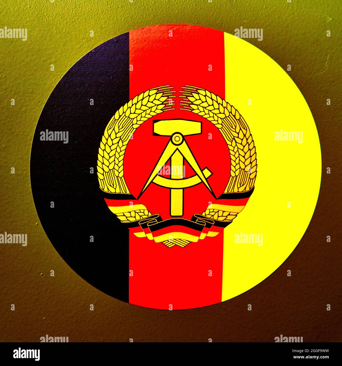 Coat of arms of the GDR, hammer, sickle and ears of grain on black-red-gold background, pasted on a military vehicle Stock Photo