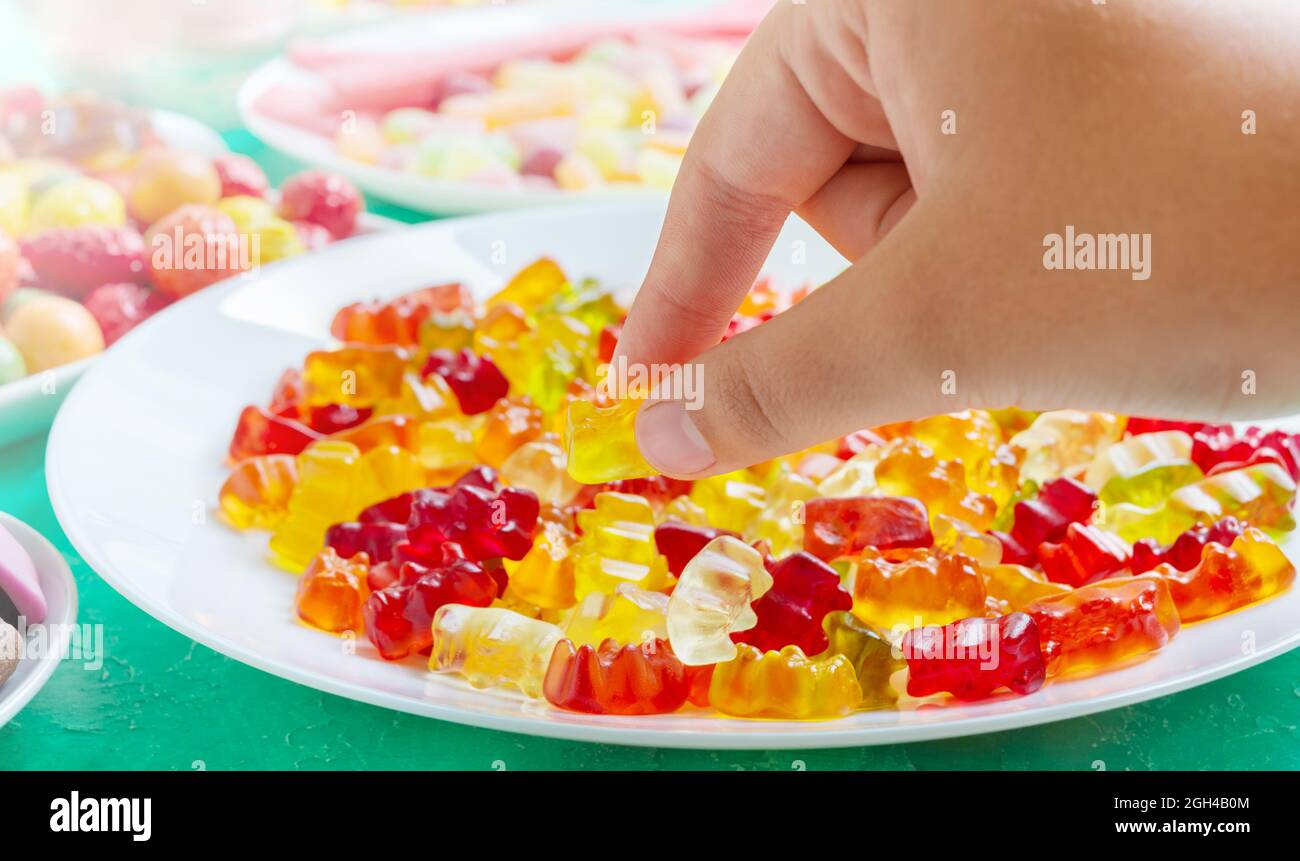 Hand takes colorful gummy bears candies of the plate. Close-up. Jelly treats for children and adults. Stock Photo