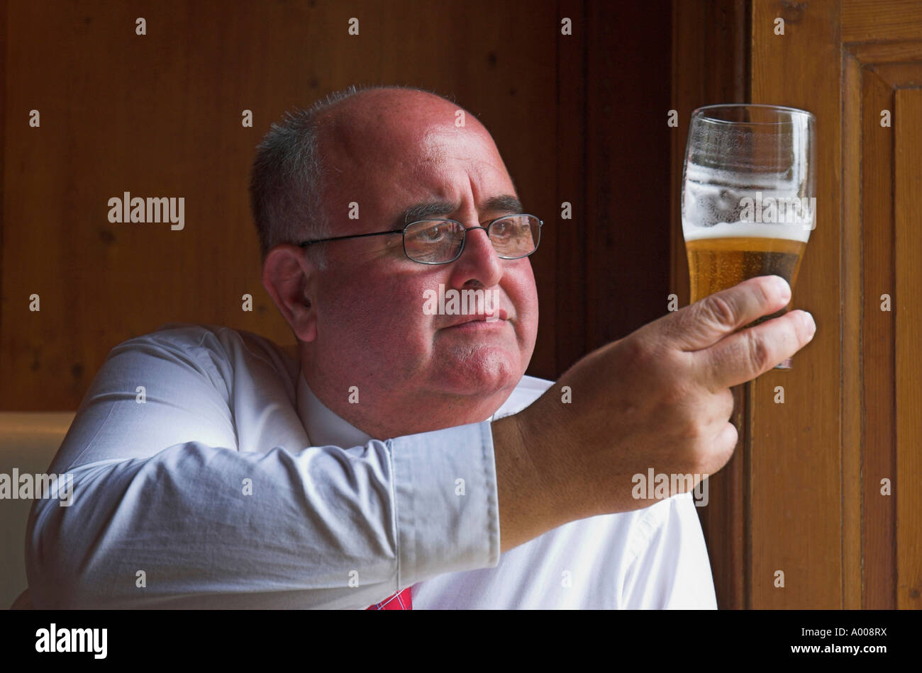 Mature man enjoying a lunchtime pint in the pub Stock Photo