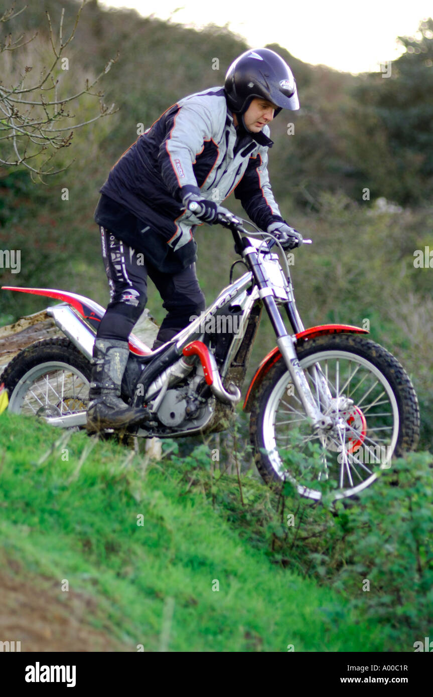 motorcycle trials rider negotiating tricky section of course on specialist built machine / motorbike Stock Photo