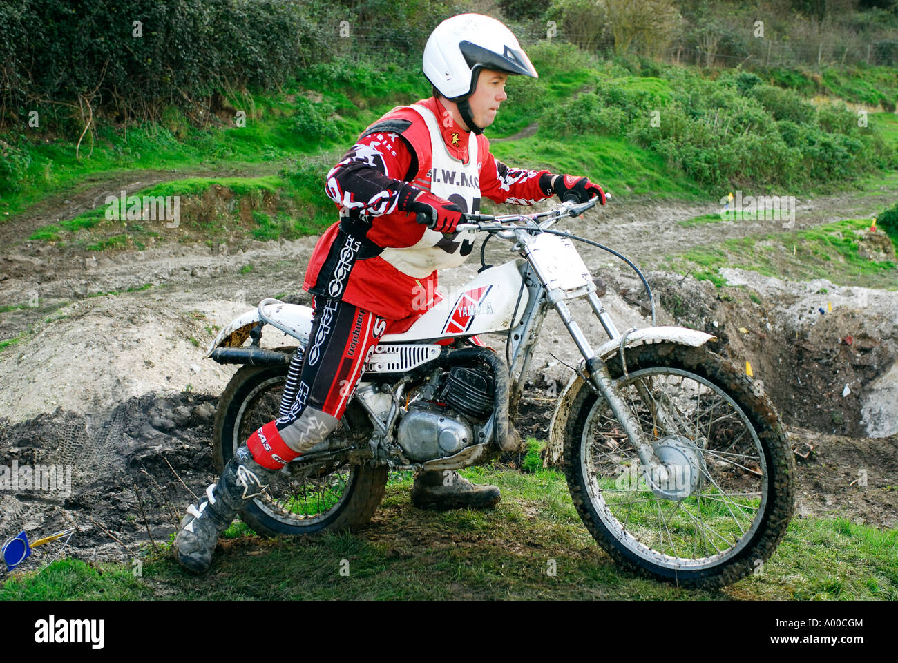 motorcycle trials rider negotiating tricky section of course on specialist built machine / motorbike - Stock Image