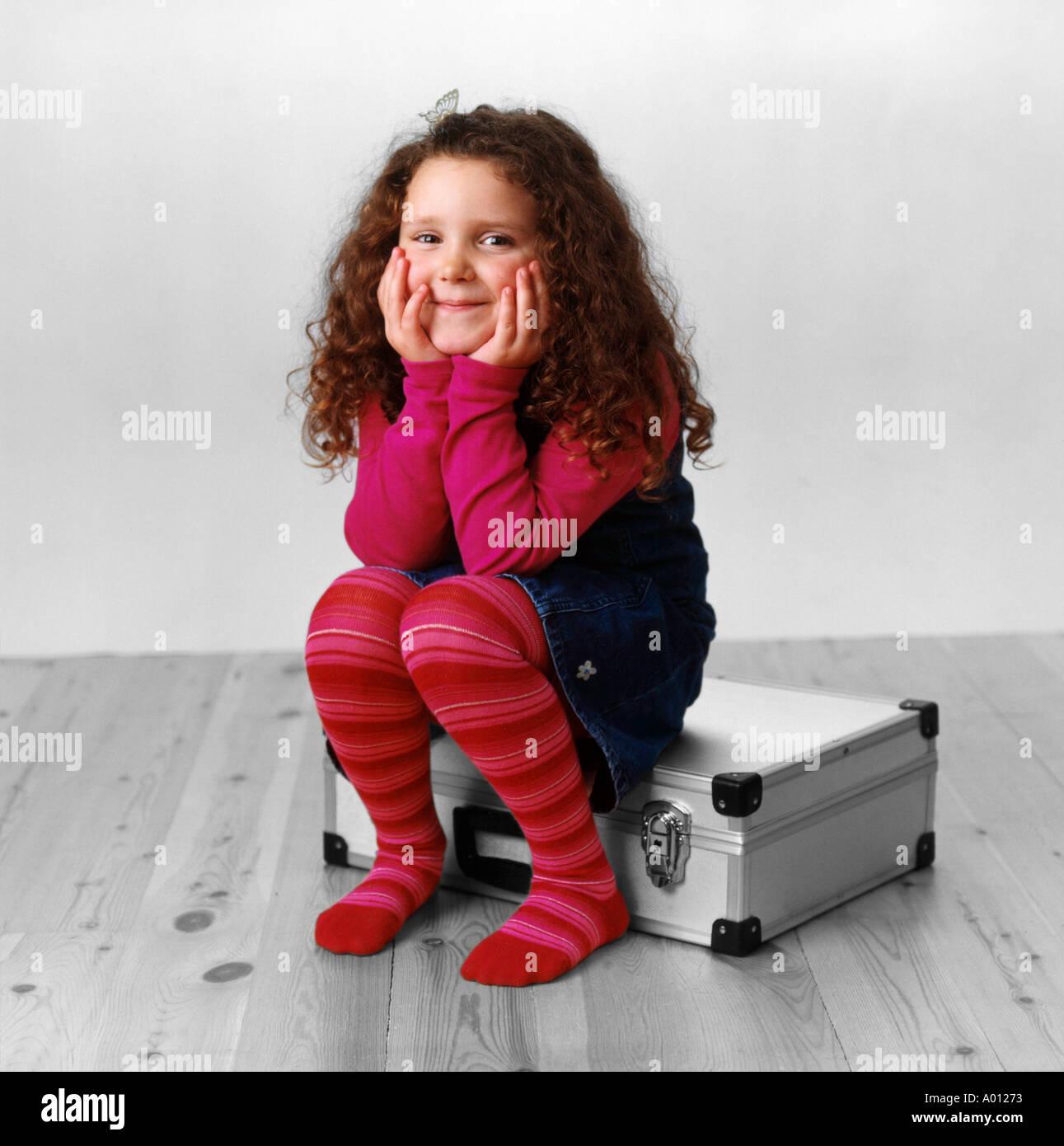 Girl smiling sitting on metal case - Stock Image