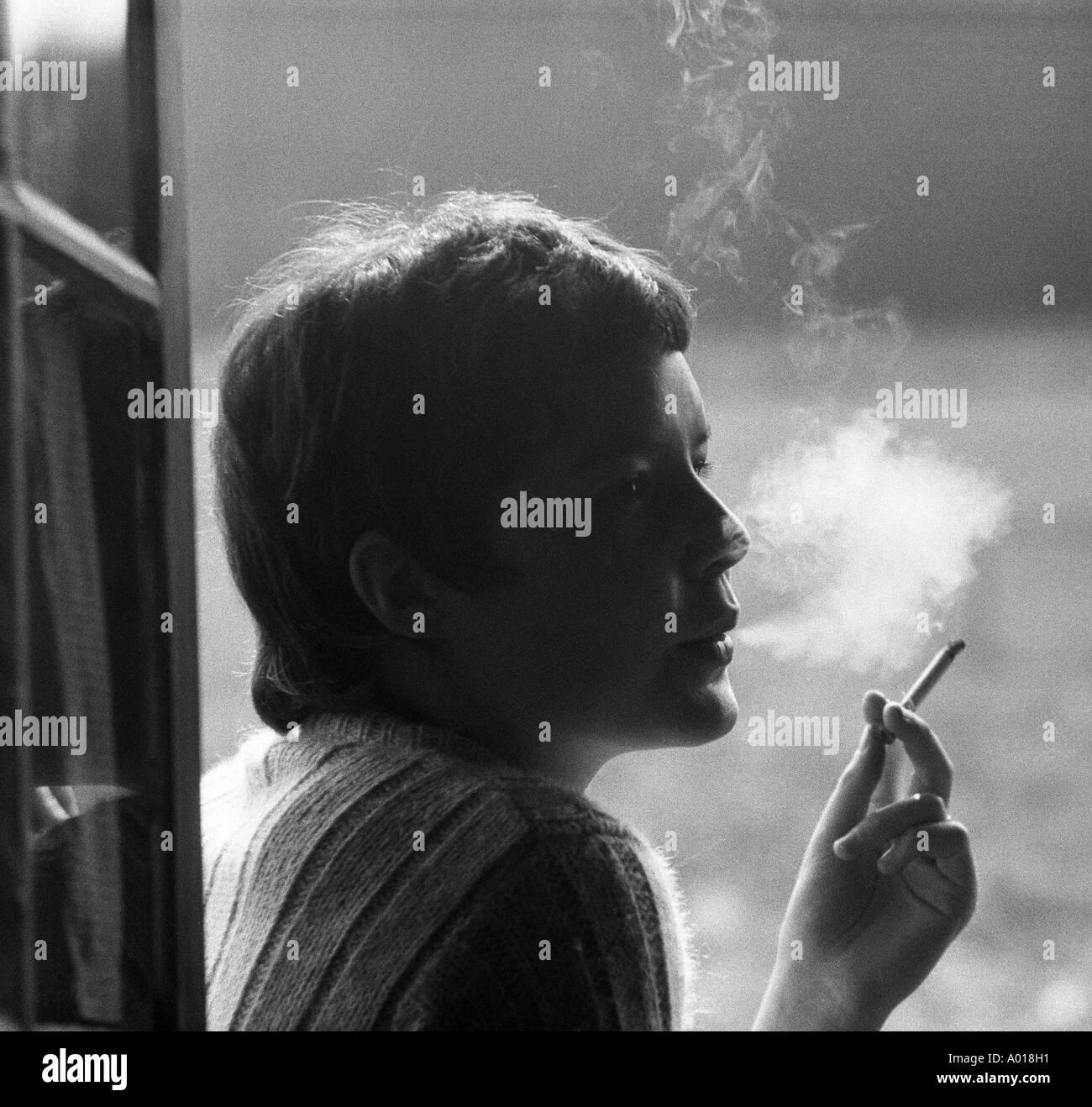 Health young girl young woman smoking a cigarette smoke back light
