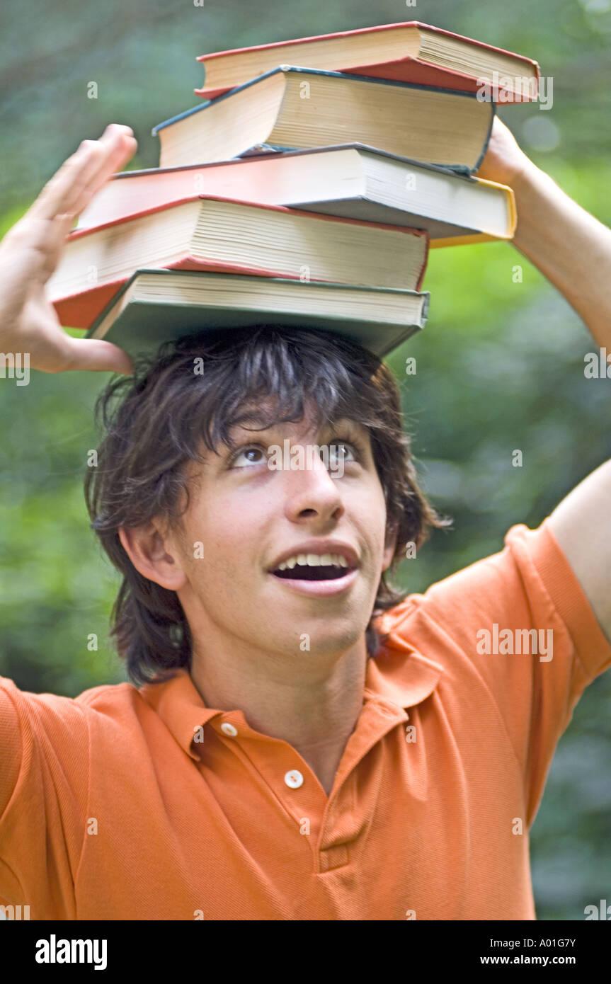 Student balancing books on his head - Stock Image
