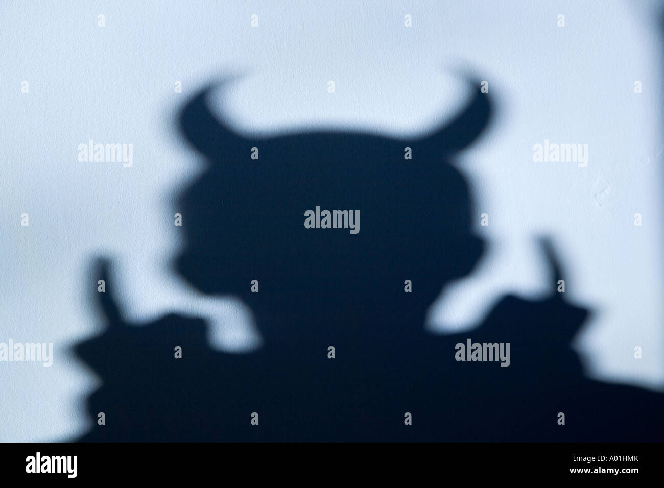 Shadow of a devil with horns on light blue wall - Stock Image