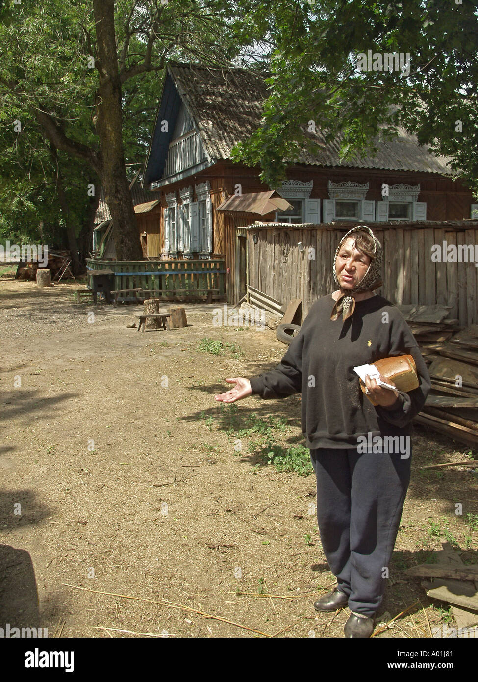 Chernobyl survivor, 58 year old woman clutching fresh loaf of bread in one arm in front of a row of houses, Chernobyl Exclusion Zone, Belarus - Stock Image