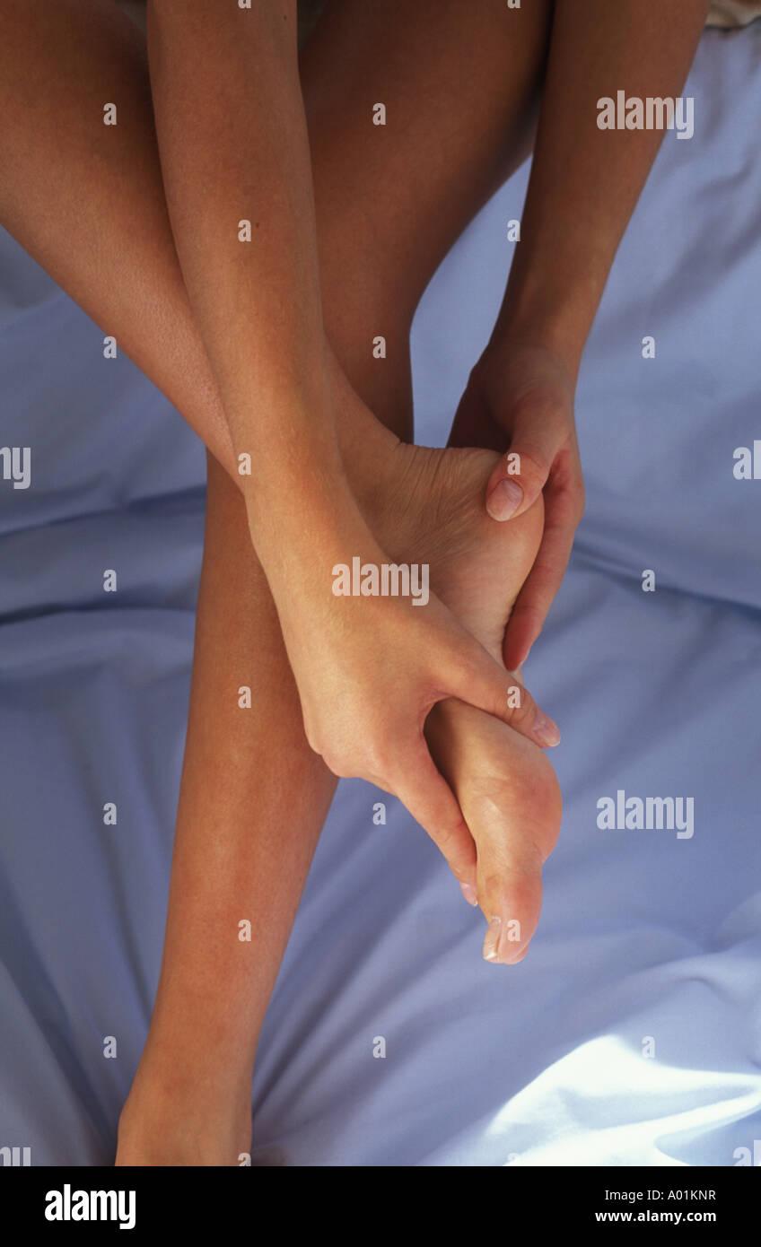 woman massaging her feet - Stock Image