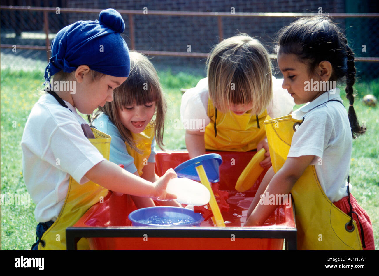 children at nursery playing with water outdoors - Stock Image