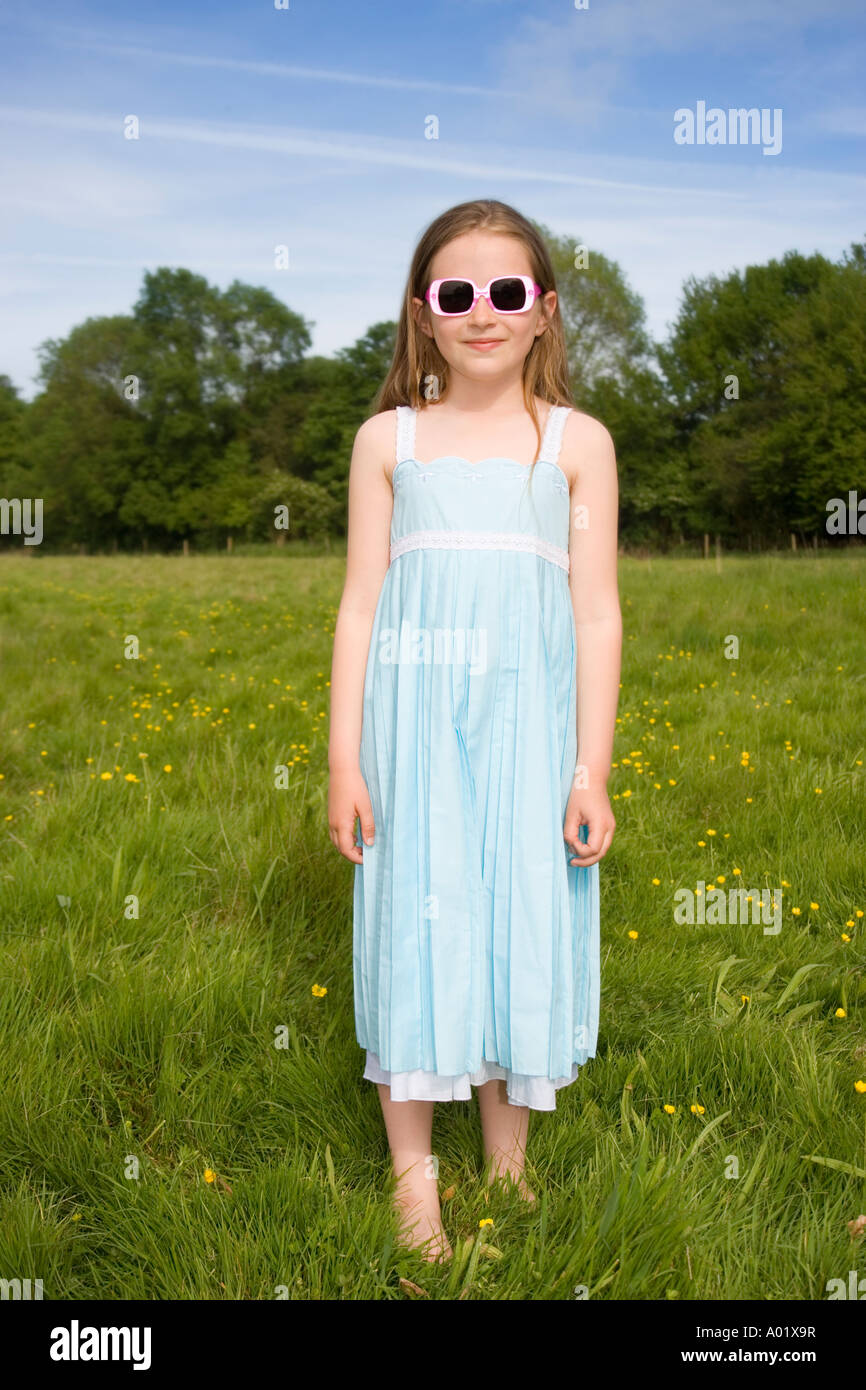 Portrait of girl wearing sunglasses standing in meadow - Stock Image