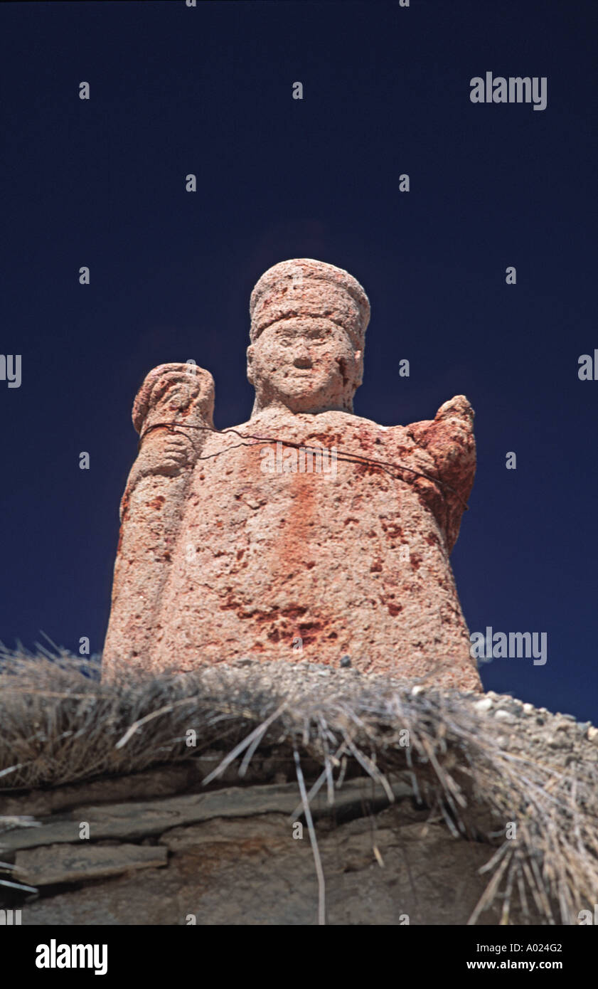 Stone sculpted bishop figurine atop an archway leading into Parinacota s 18th century church Lauca National Park Chile - Stock Image