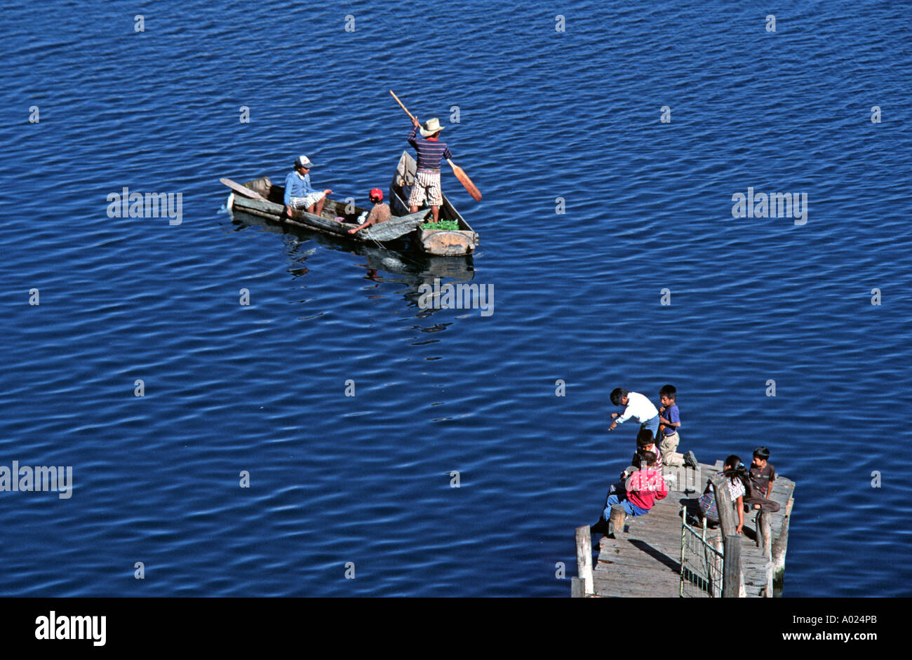 Fishing from local traditional style canoes whilst youngsters fish from the jetty Lake Atitlan Santiago Atitlan Guatemala - Stock Image