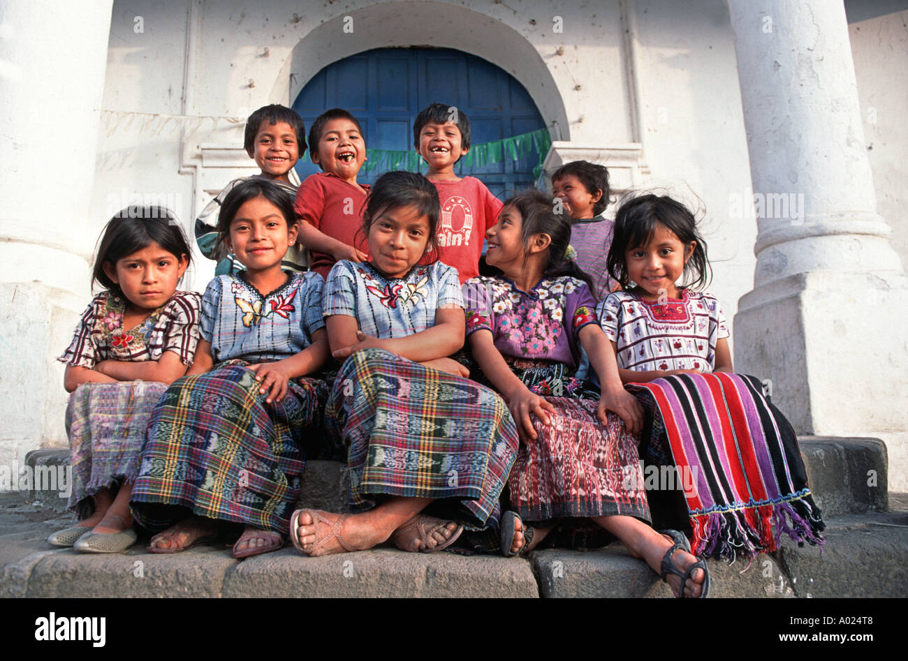 A group Maya girls and boys from Santiago Atitlan seated at the top of the Church steps Lake Atitlán Guatemala - Stock Image