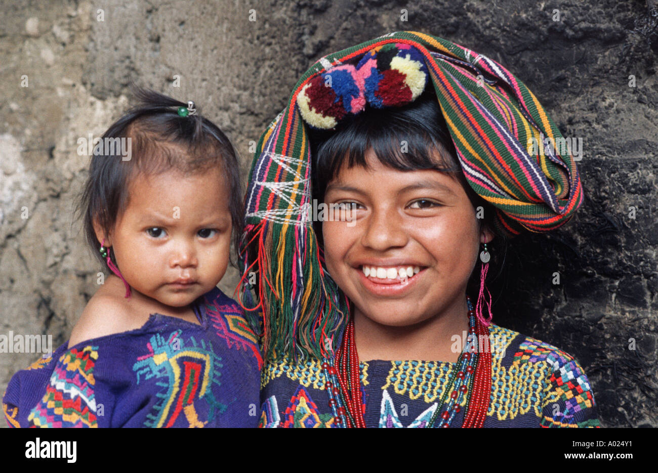 Young Maya woman wearing the brocaded costume of her community holding baby Chajul Ixil Triangle El Quiche Guatemala - Stock Image
