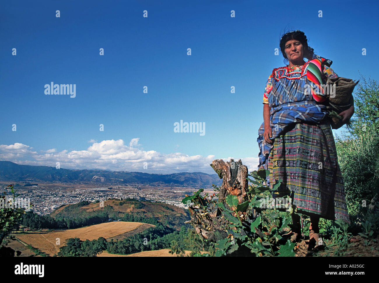 Portrait of a flower picker standing on a hillside with the town of Quetzaltenango in the distance Guatemala - Stock Image