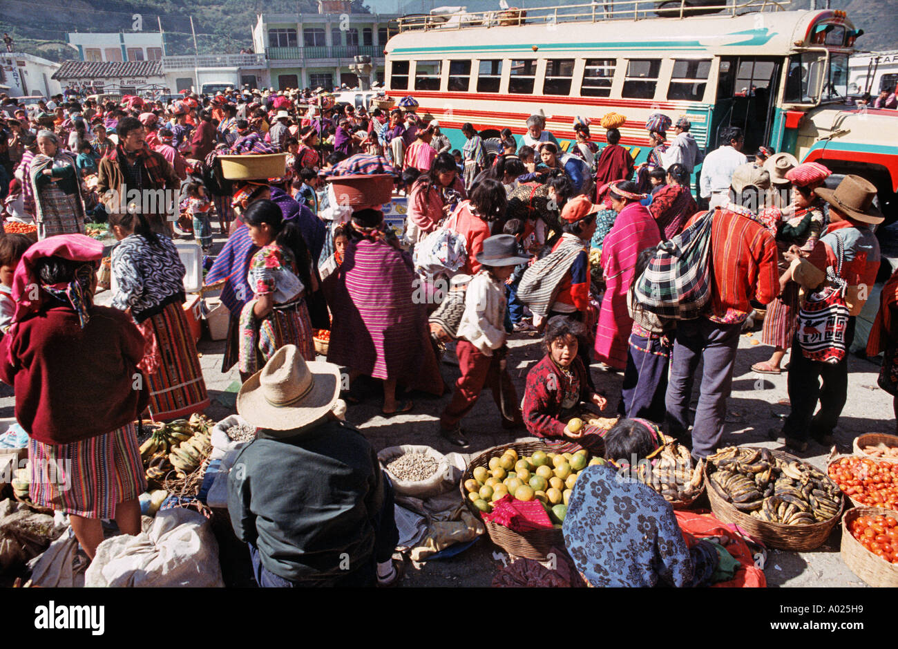Crowded market scene with bus Zunil town Guatemala Central America - Stock Image
