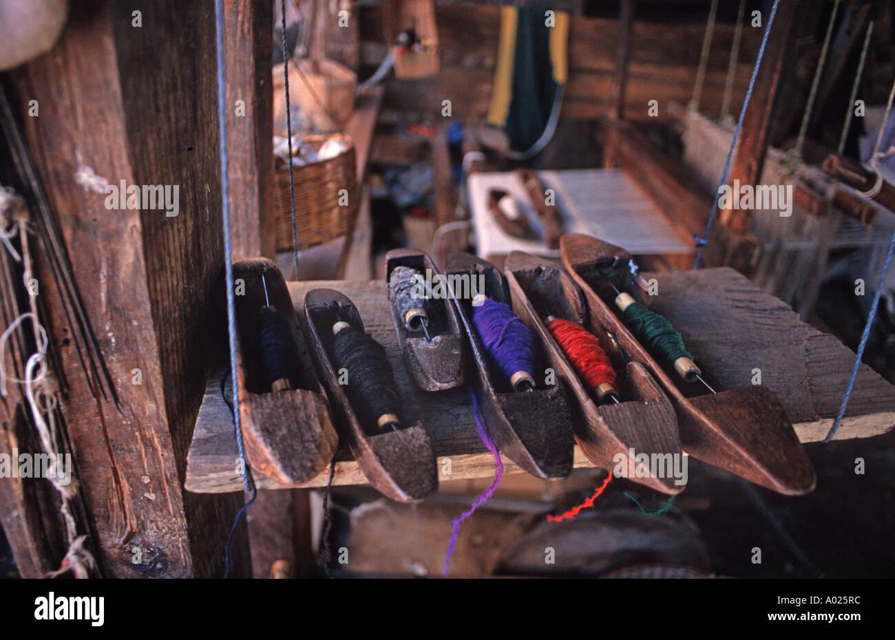 Bobbins holding colourfully dyed handspun woollen thread Sitting beside a treadle operated loom Momostenango Guatemala - Stock Image