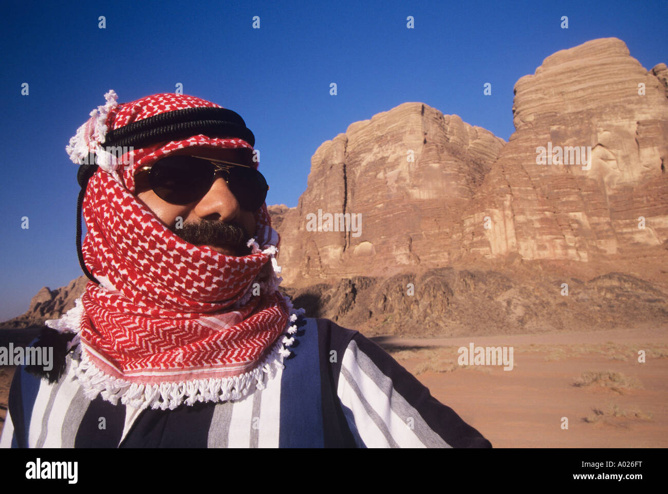 Arab Man in turban, Wearing Sunglasses, standing in desert landscape - Stock Image