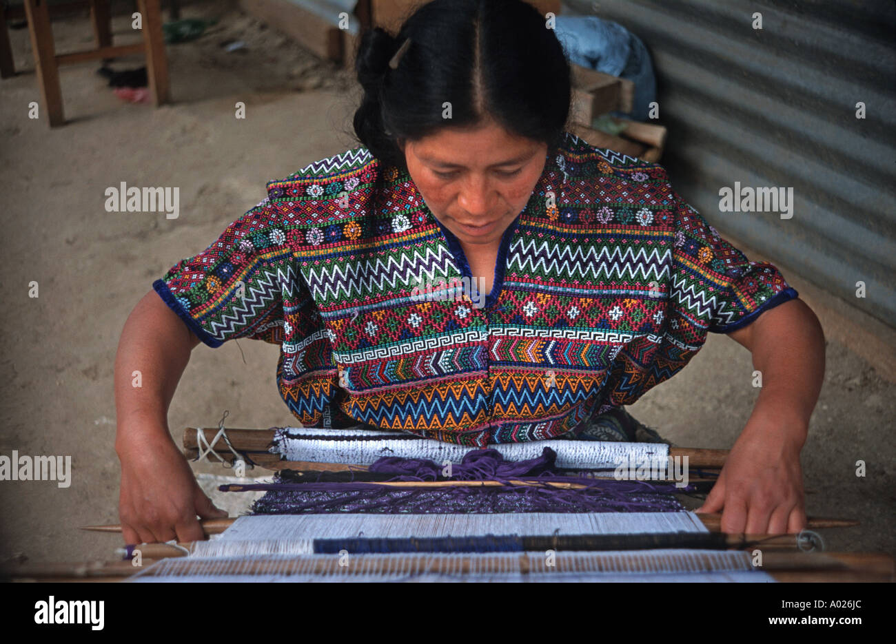 Maya woman from San Martin Jilotepeque working on a hipstrap loom and weaving a Maya style blouse called a huipil Guatemala - Stock Image