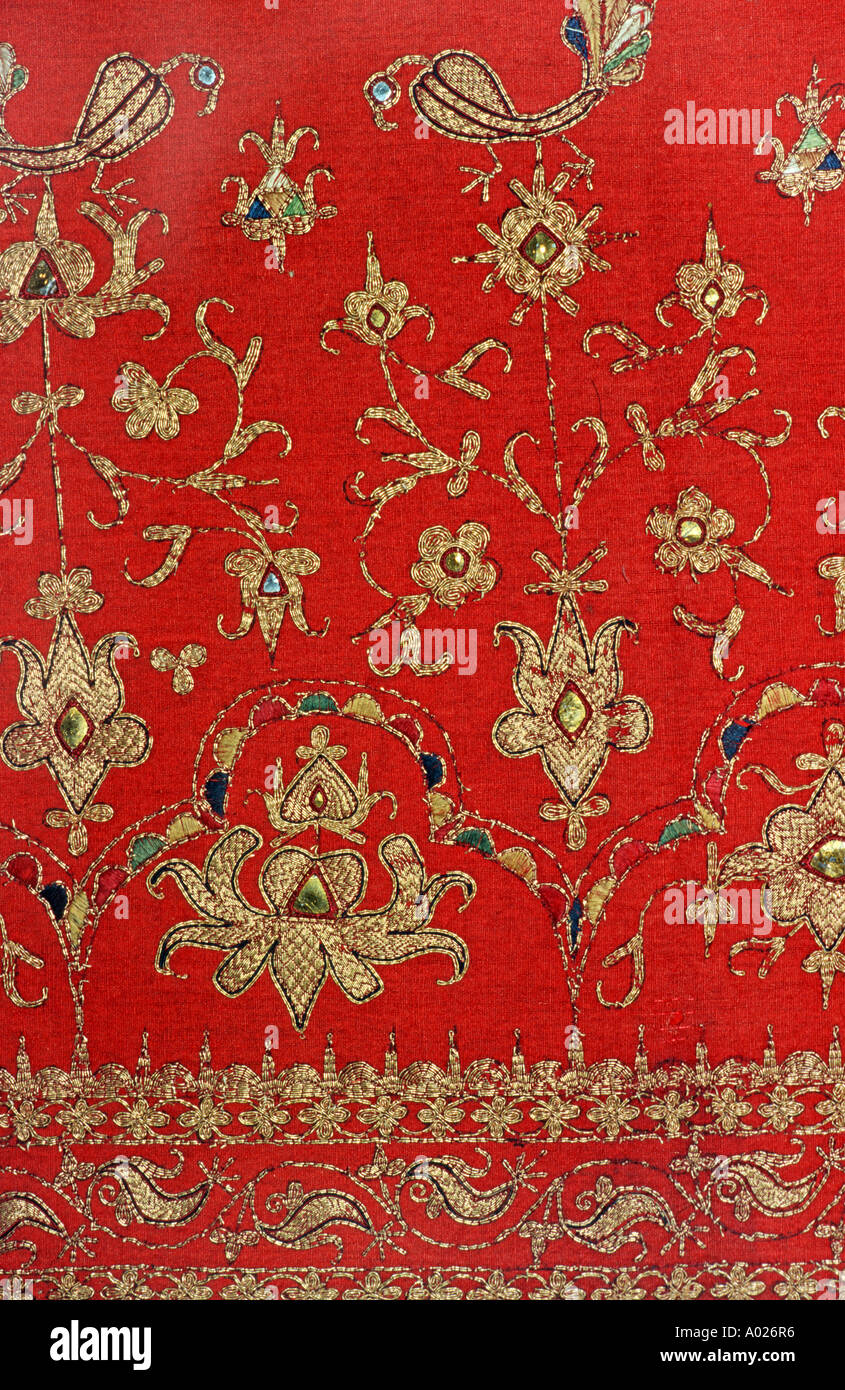 Woven and embroidered textile with golden threads on a red groundcloth Sumatra Indonesia Southeast Asia - Stock Image
