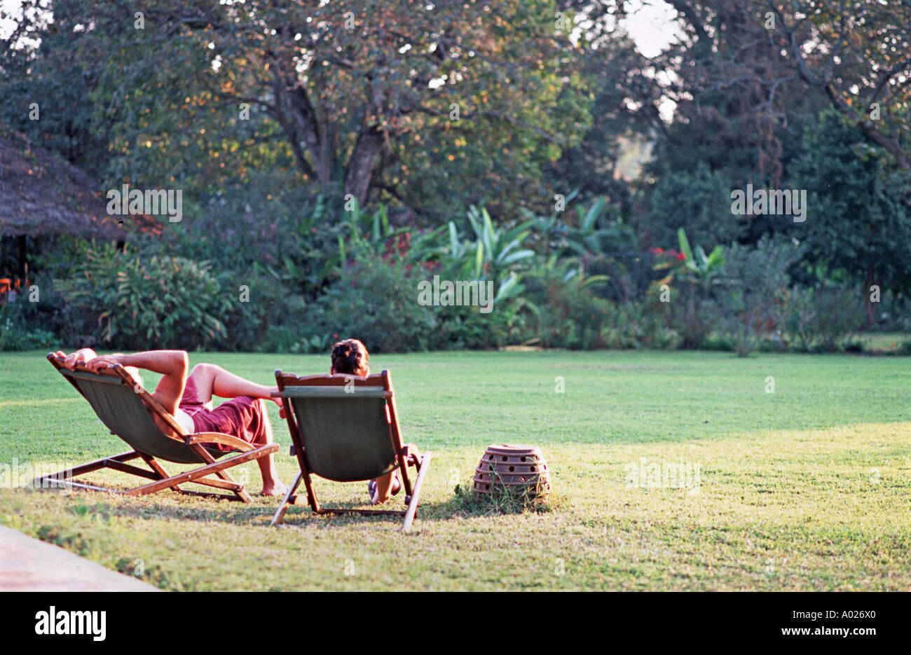Western couple relaxing in sunloungers at sundown att the Moivaro Coffee plantation Arusha Tanzania A popular place Stock Photo