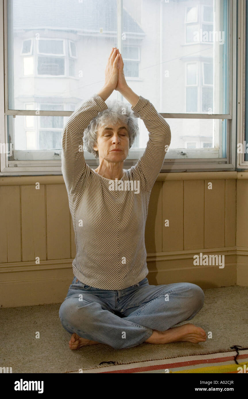 middle aged woman practising yoga at home in the window of her house - Stock Image