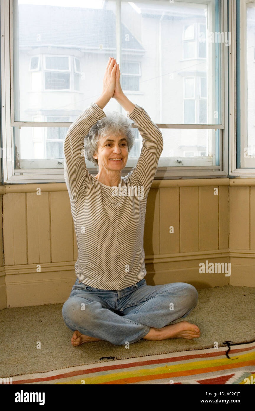 A middle aged woman practising yoga at home in the window of her house, Wales UK - Stock Image
