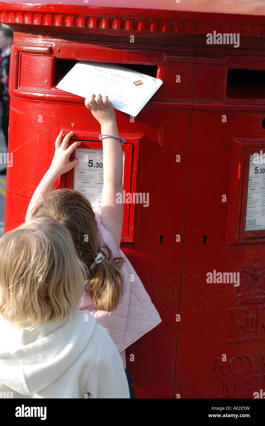 Young girl posting a letter in to a large red British Post Office box - Stock Image