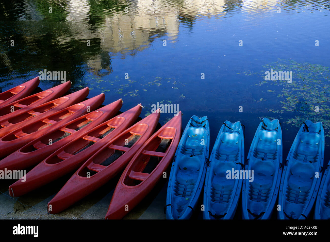 Kayaks lined up along the Lot riverbank at sunset, Puy-L'Eveque, Lot, France. Stock Photo