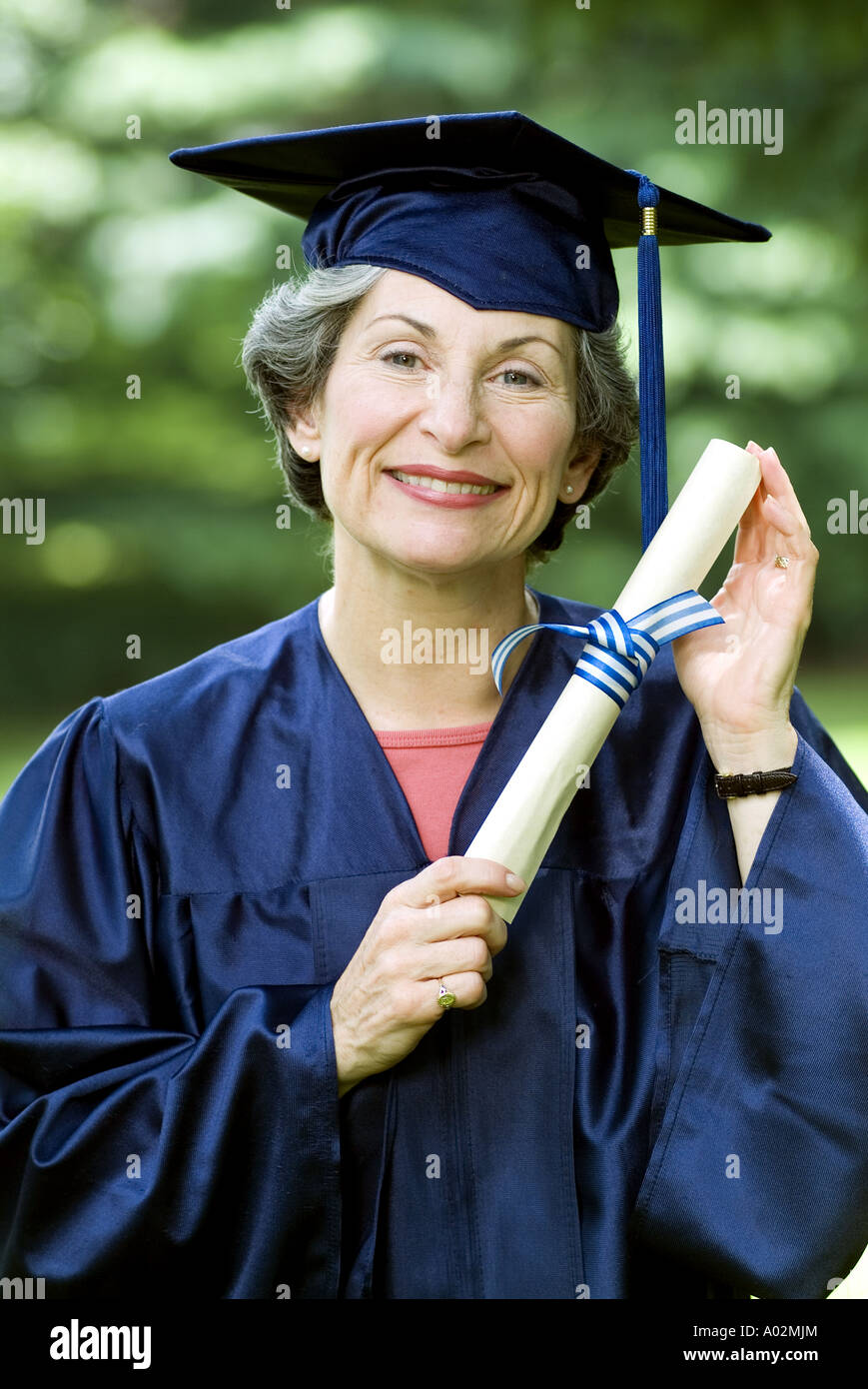 Smiling senior citizen woman college graduate with diploma - Stock Image