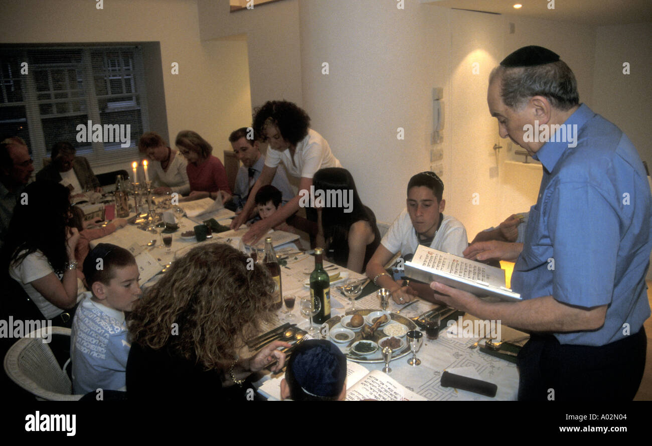 Jewish passover with the head of the family reading from the Haggadah London - Stock Image