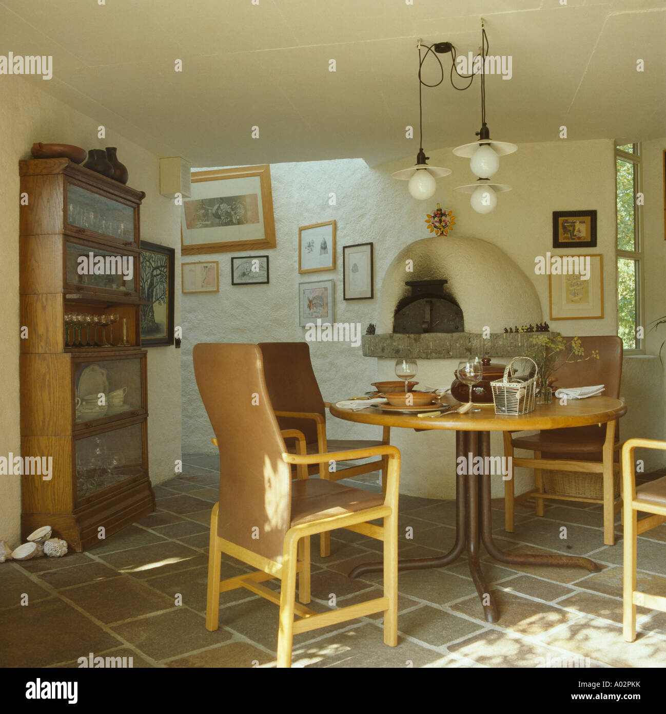 Modern chairs and table on paved floor in traditional Swedish country cottage - Stock Image