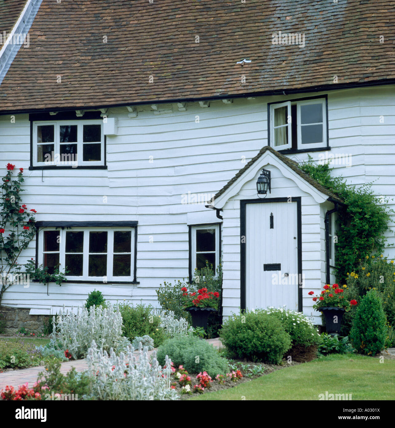 Traditional white-painted wooden cottage in country - Stock Image