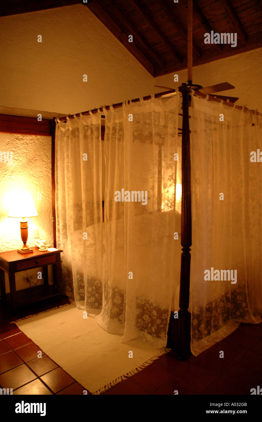 Tropics four poster bed mosquito netting Casa de Campo Resort Dominican Republic luxury suite mega resort caribbean islands isla - Stock Image