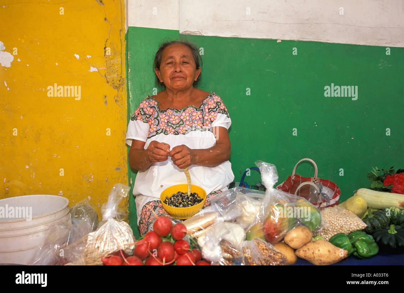 Mexico maya woman at market mayan produce vegetables tomatoes yucatan colorful wall colorful costume traditional dress - Stock Image