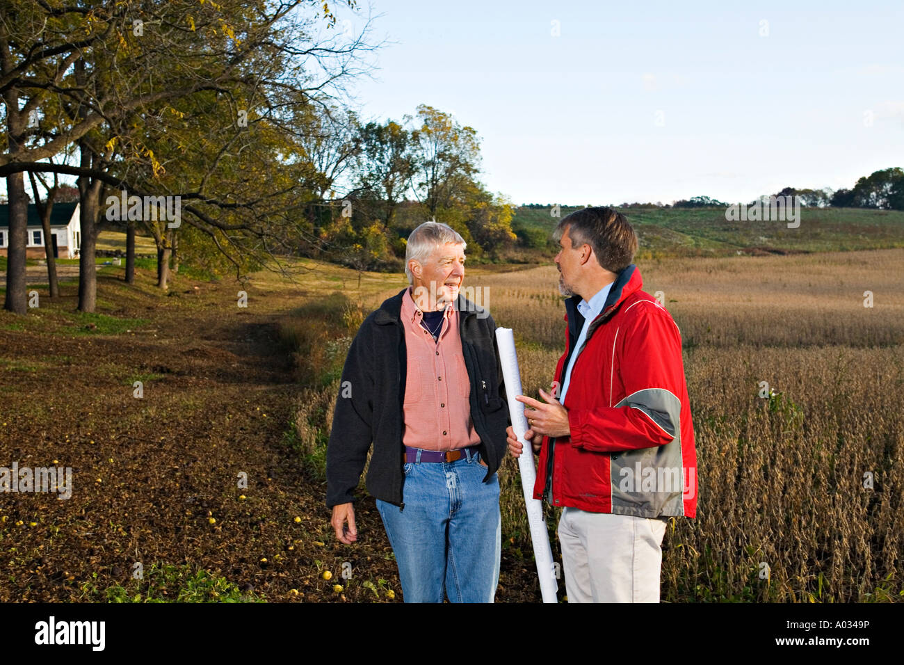 ILLINOIS Grayslake Two men discuss plans for site talk together about location usage man hold roll of blueprints - Stock Image