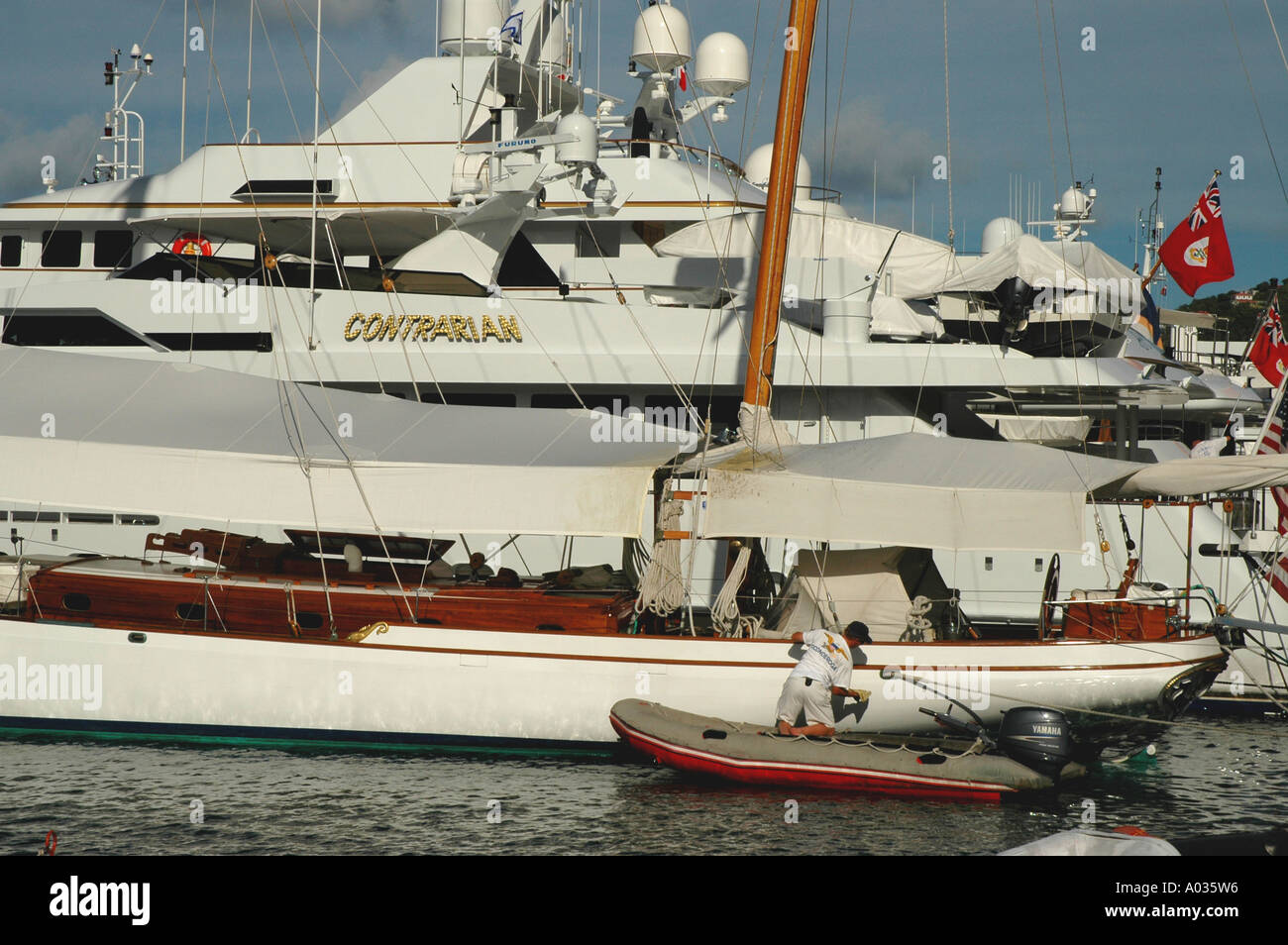 St Barths St Barts Gustavia Harbor luxury yachts crewman cleaning hull - Stock Image