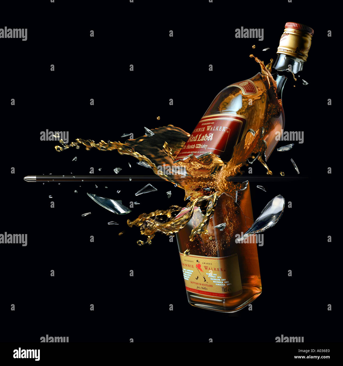 whiskey bottle breaked by a bullet with splash - Stock Image
