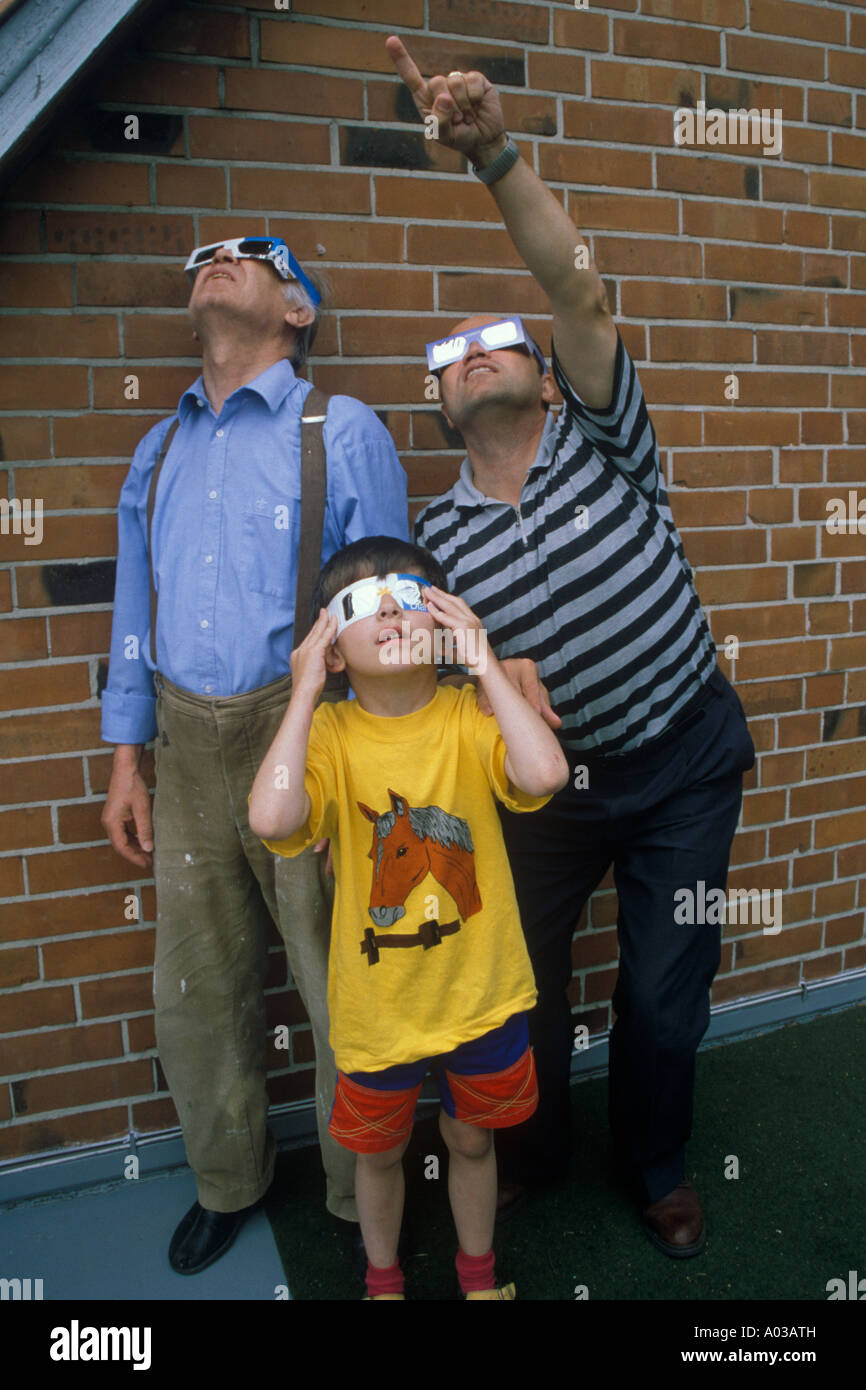 grandfather, father and son watching a penumbral solar eclipse Stock Photo
