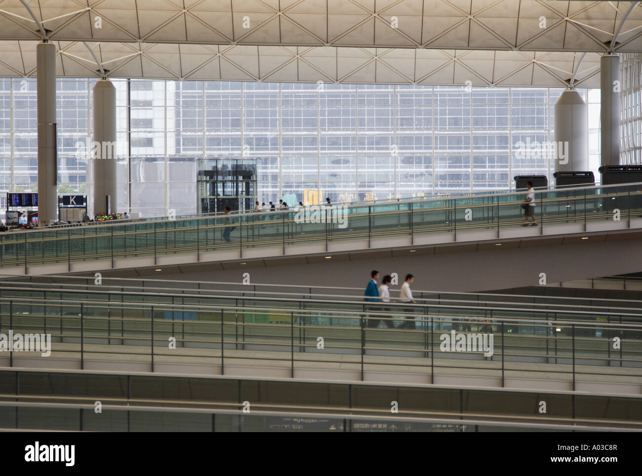 Passengers Walking Along Ramps At Hong Kong International Airport - Stock Image