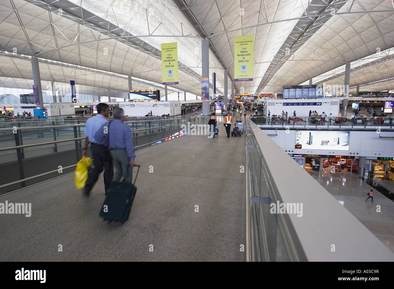 Two Passengers Walking Into Hong Kong International Airport - Stock Image