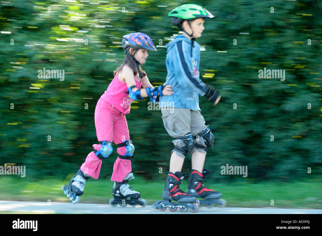 young skater pushing her big brother - Stock Image