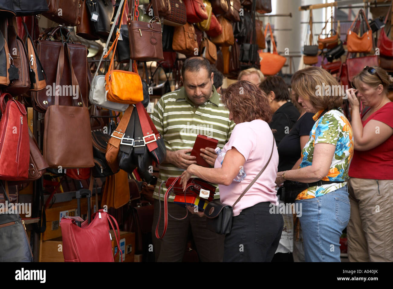 salesman-and-customers-at-handbag-display-in-outdoor-market-firenze-A040JK.jpg