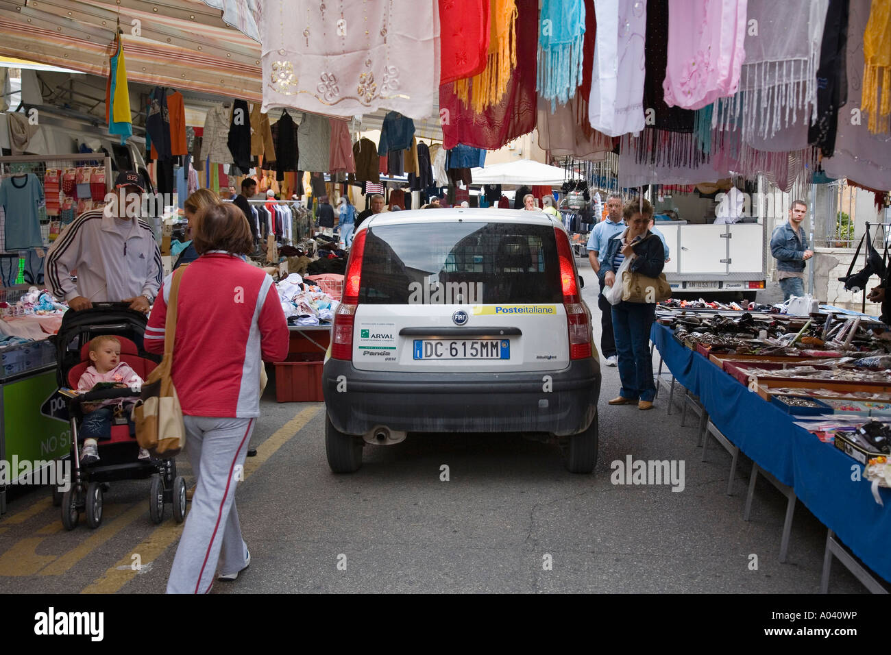 Italian postal vehicle drives between booths on crowded street during weekly market day Marsciano Italy PG - Stock Image