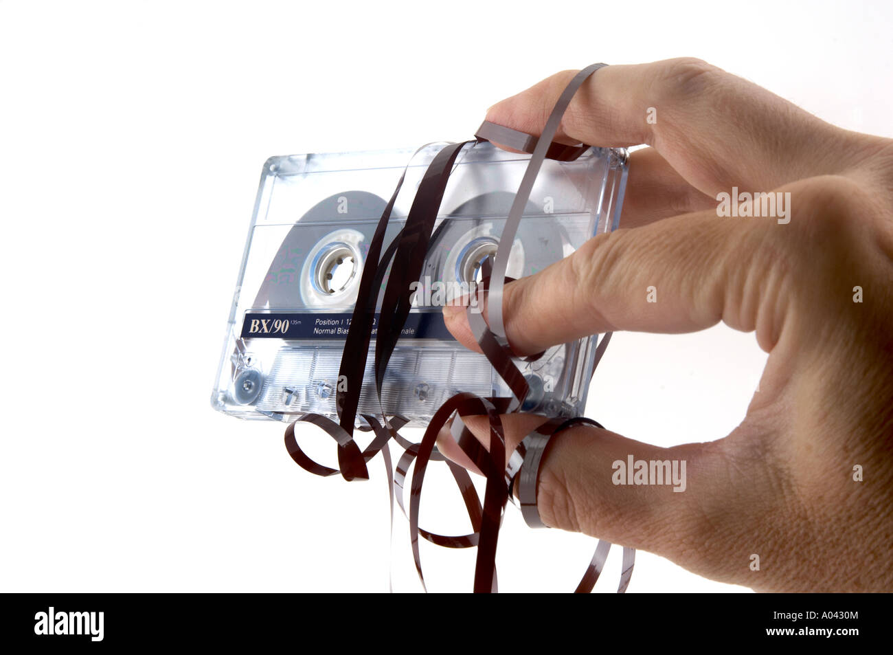 close up of a hand with a compact cassette with tangled tape - Stock Image