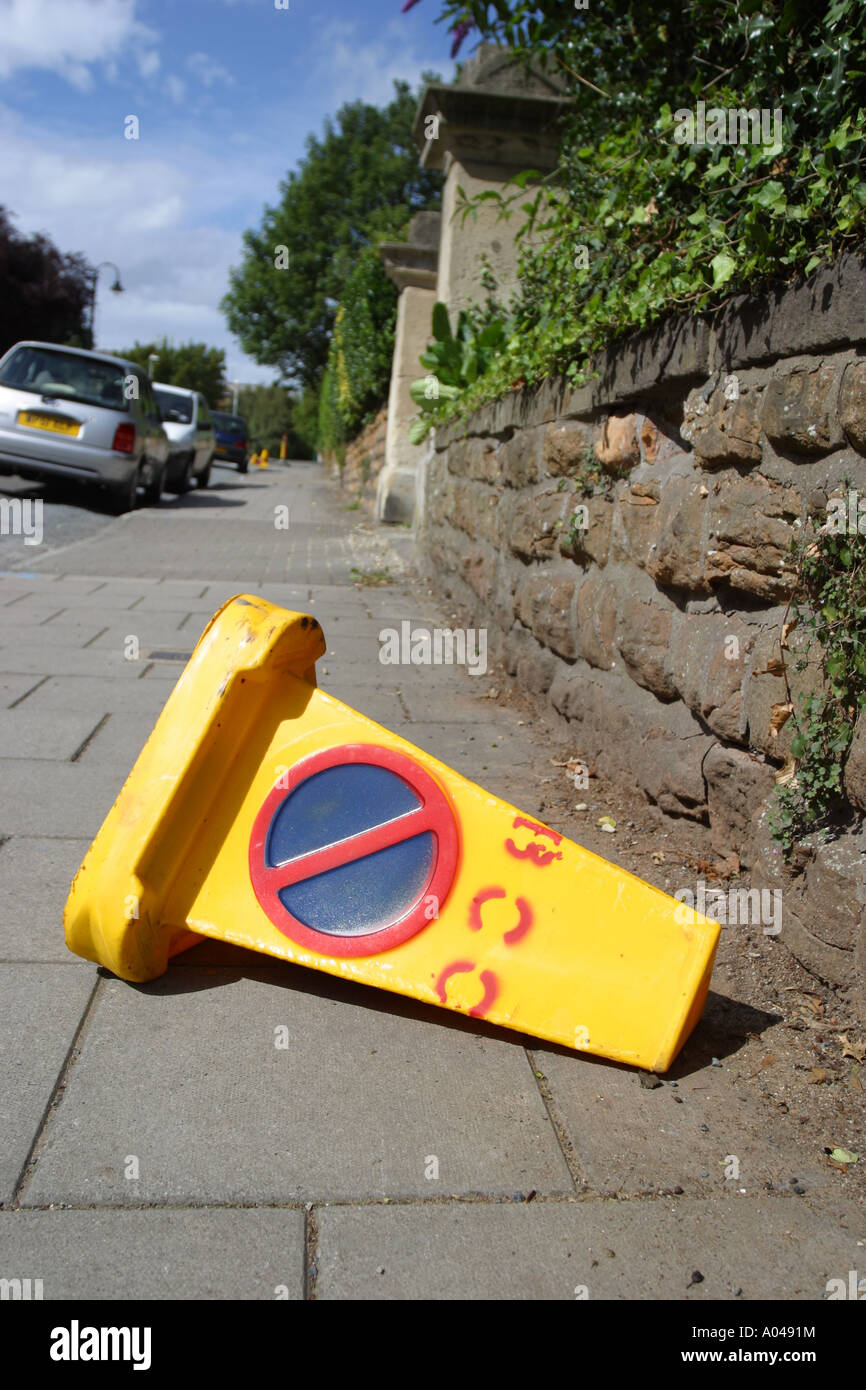 No parking plastic cone tipped over blocking pedestrian pavement - Stock Image