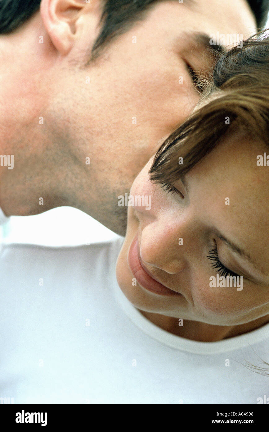 Close up portrait of a young man kissing a woman's ear - Stock Image