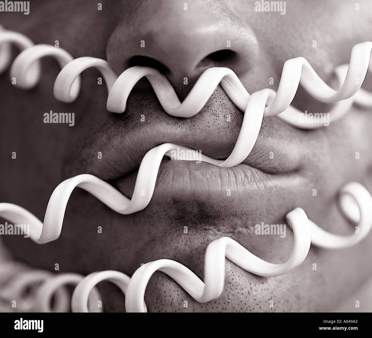 Telephone cord wrapped around a man's mouth - Stock Image