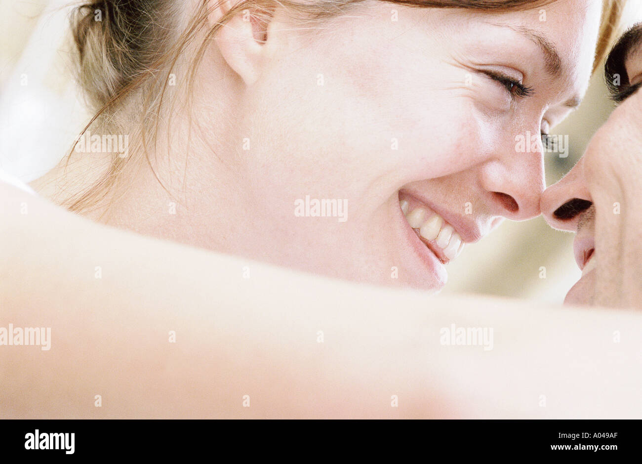 Close up detail of young couple   heads together  looking into each others eyes - Stock Image