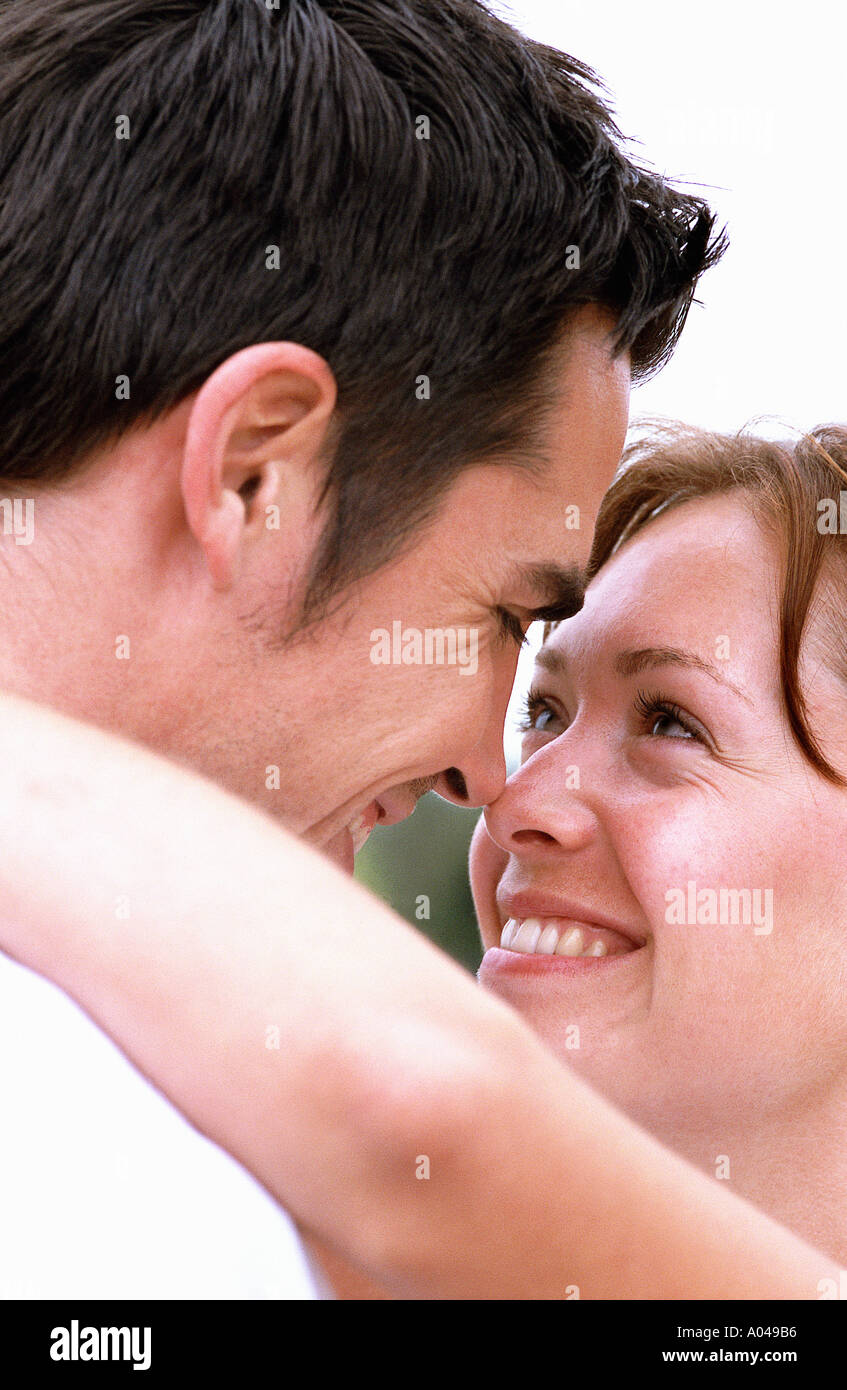 Close up portrait of a young couple embracing  looking into each others eyes - Stock Image