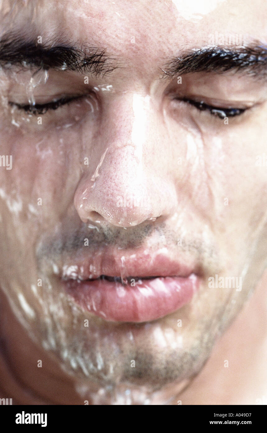 Portrait of a young man with water running down his face  eyes closed - Stock Image